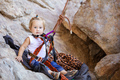 Little girl fastened to rock climbing gear and sitting on cliff