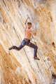 Male climber jumping on handholds on a cliff