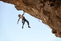 Male rock climber hanging with one hand on on a cliff