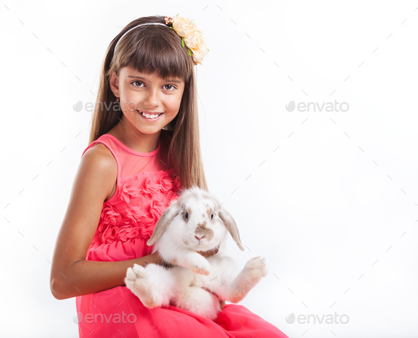 Young girl holding flap-eared rabbit against white