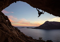 Young man climbing in cave against beautiful view of coast below