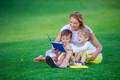 Young woman reading book to her sons while sitting on grass