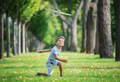 Boy playing with toy glider in park on summer day