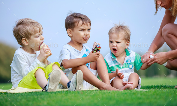 Two older boys eating ice cream, young woman wiping hands of youngest son