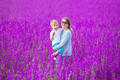 oung woman and her son having fun in purple field