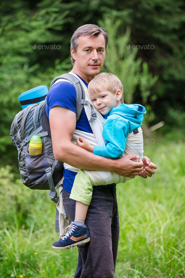 Caucasian man carrying his son in sling while hiking