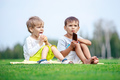Two young boys eating ice cream in a park