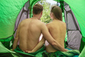 Rear view of a naked young couple sitting in a tent