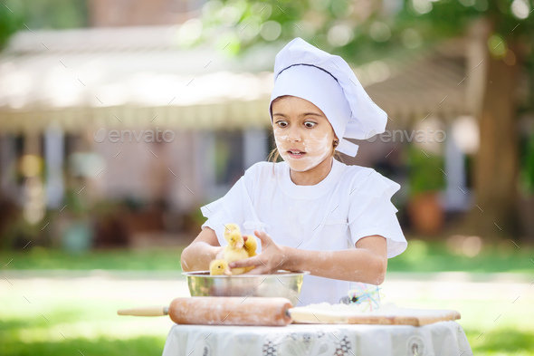 Astonished little chef holding ducklings while cooking outdoors