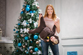 Young woman playing with little son dressed in monkey costume beside Christmas tree
