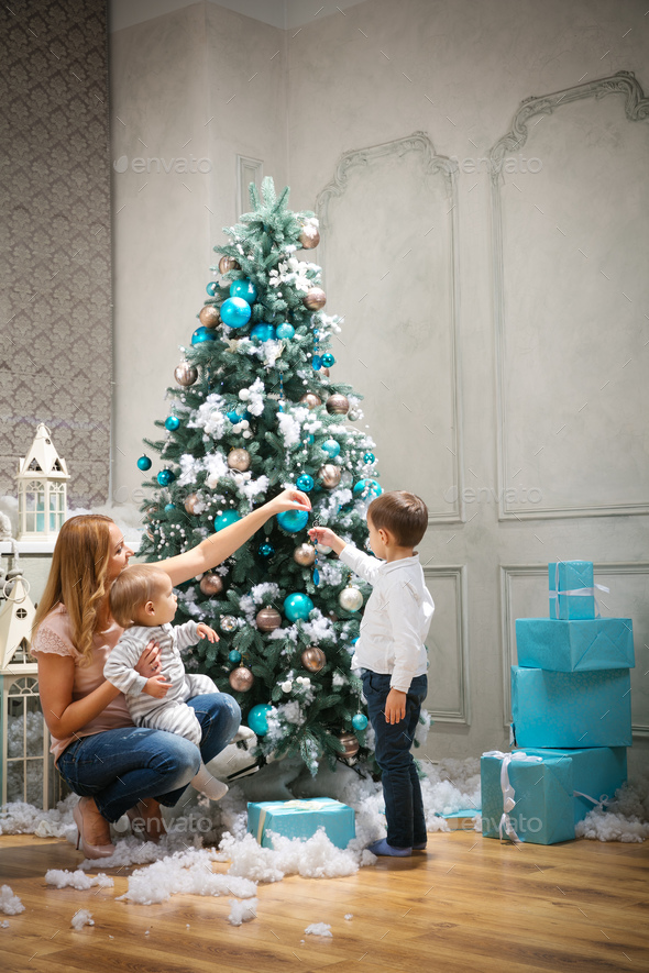 Young woman with two sons decorating on Christmas tree at home - Stock Photo - Images