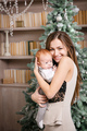 Young mother holding baby son and smiling while standing against Christmas tree