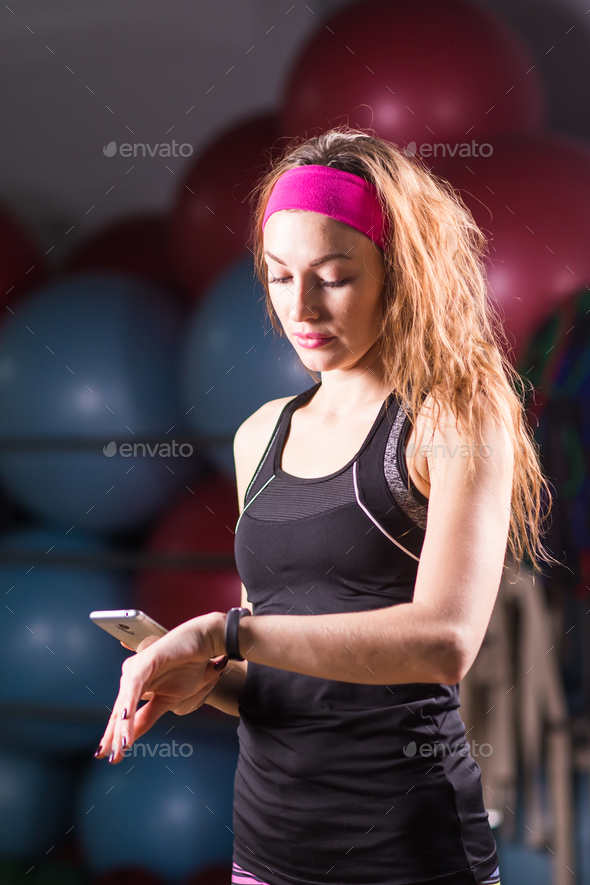 woman with heart-rate watch and smartphone in gym - Stock Photo - Images