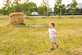 Happy laughing baby boy running on summer or autumn field