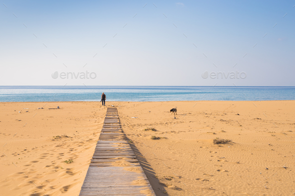 Man with dog walking on the wooden path on the beach and looking into the distance of the ocean - Stock Photo - Images