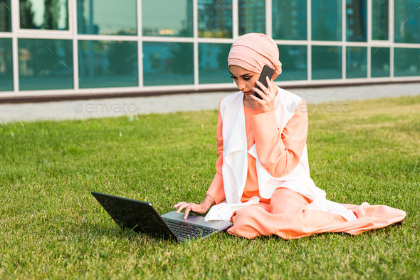 Young Muslim Woman Using Mobile Phone and Laptop In Park - Stock Photo - Images