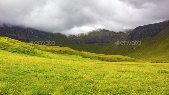 Green grass and mountains a cloudy day at Faroe Islands - Stock Photo - Images