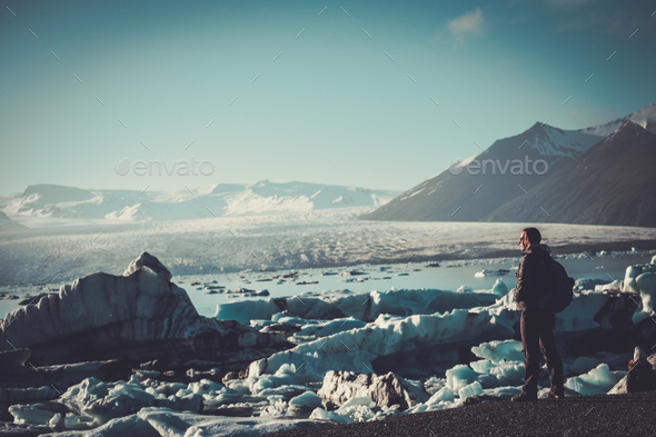 Woman explorer lookig at Jokulsarlon lagoon, Iceland. - Stock Photo - Images