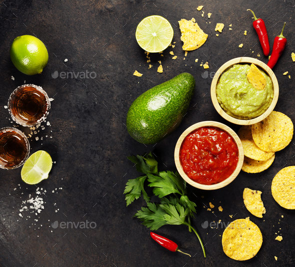 Green Homemade Guacamole with Tortilla Chips, Salsa and tequila - Stock Photo - Images