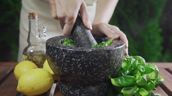 VideoHive Housewife Grinds the Basil for Pesto Sauce Outside Cooking Food Spicy Food Vegetarian Meal 20314807