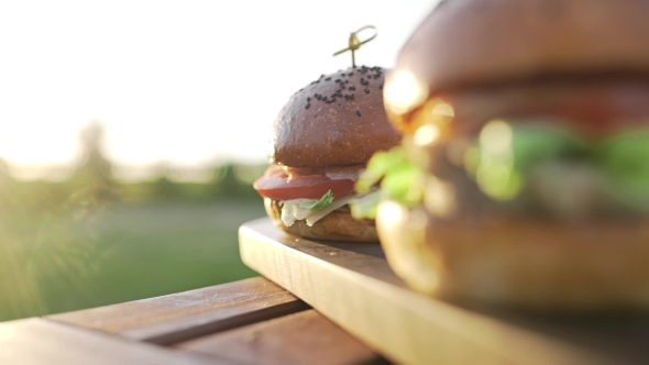 VideoHive Hot Burgers on the Wooden Board in the Sunset Sunlight at the Coutriside Fast Food Meals Cooking 20314812