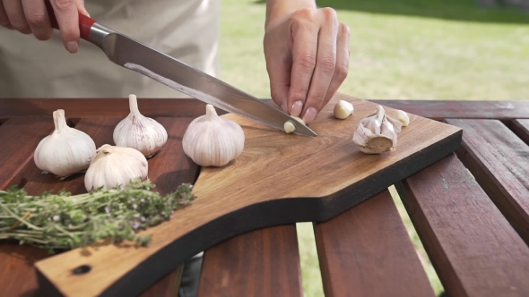 VideoHive The Cook Slices Garlic on the Wooden Board By Sharp Knife Outside Cooking Outside Cooking Healthy 20314824