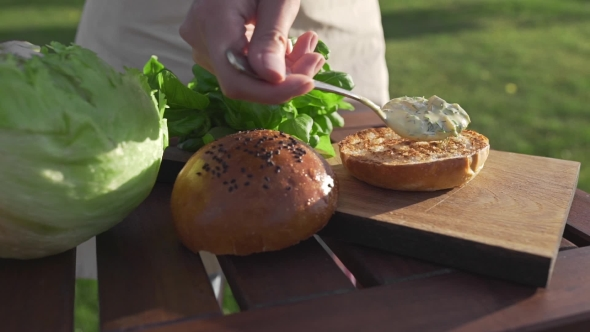 VideoHive The Cook Puts Sauce To the Bun and Makes Burger Outside Countryside Cooking Open Air Cooking Meal 20314827