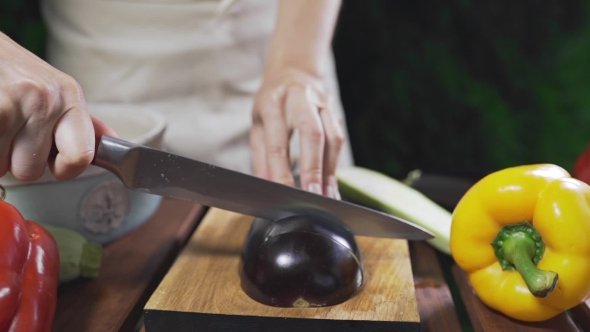 VideoHive The Cook Cuts the Eggplant on the Wooden Board Outside for Making Vegetarian Meal Vegetable Cuisine 20314833