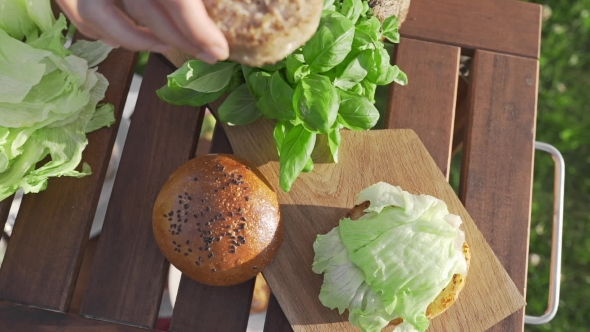 VideoHive The Cook Puts Cutlet To the Bun and Makes Burger Outside Countryside Cooking Open Air Cooking 20314843