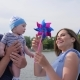 Woman Entertains Baby with Help Pinwheel on Loch, Weekend of Male Since Spouse and Kid on Sailing