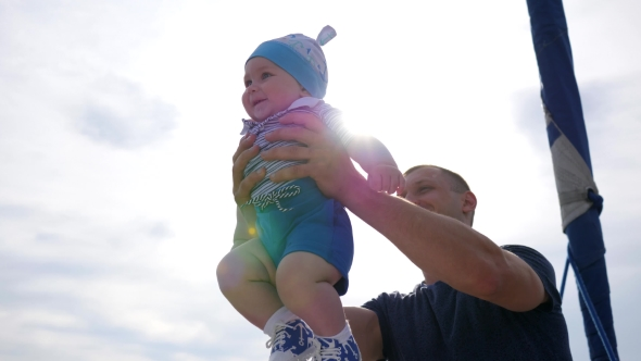 Little Kid in Father's Strong Hands in Sunlight, Child Into Hands of Dad on Blue Sky Background