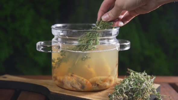 VideoHive The Cook Puts Bunch of Thyme To the Hot Shrimp Broth in the Glass Pan Standing on the Wooden Board 20320860