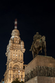 Public Statue and Skyscraper at Night