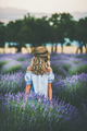 Young blond woman traveller standing in lavender field, Isparta, Turkey