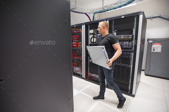 IT Engineer Carrying Blade Server While Walking In Datacenter - Stock Photo - Images