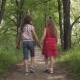 Two Little Girls Hold Hands and Walk Down the Green Alley. Children Walk Outdoors
