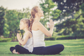 Mother and daughter doing yoga exercises on grass in the park.