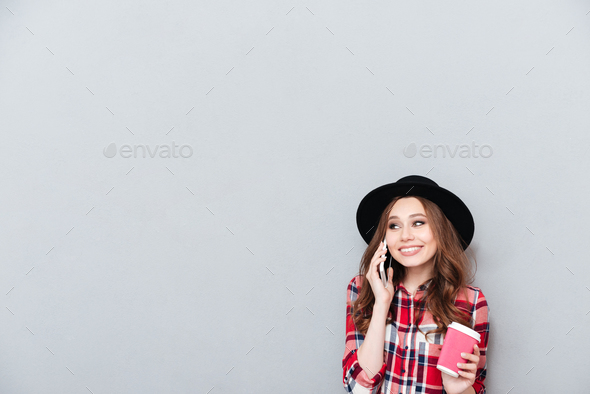 Casual smiling woman in hat talking on mobile phone