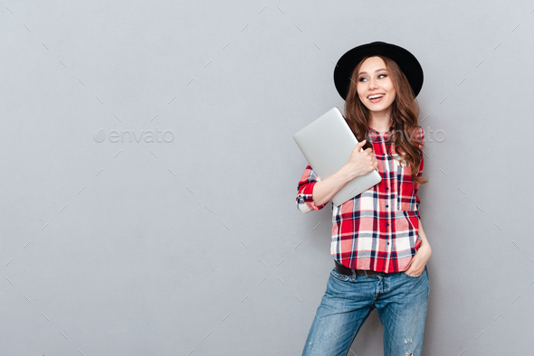 Smiling woman in plaid shirt holding laptop and looking away