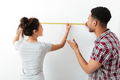 Happy young couple standing and using measuring tape