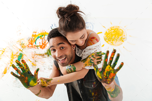 Smiling young couple painting with brushes by hands and hugging