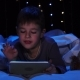 Little Boy Is Lying on a Bed Holding a Laptop and Watching a Cartoon. Bokeh Background