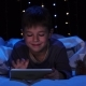 Child Is Lying on a Bed Holding a Laptop and Watching a Cartoon. Bokeh Background