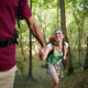 Young Couple Trekking In Forest And Holding Hands - PhotoDune Item for Sale