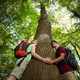Environmental Conservation: Young Hikers Embracing Large Tree - PhotoDune Item for Sale