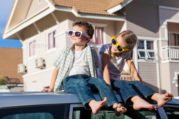 Happy children getting ready for road trip on a sunny day.