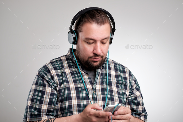Cheerful young man using earphones and listening to music from mobile phone over grey background