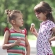 Carefree Children Eat Ice Cream in Summer Park. Two Little Girls Having Fun Talking and Smiling