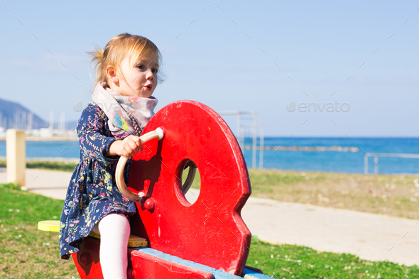 summer, childhood, leisure and people concept - happy little girl on children playground - Stock Photo - Images