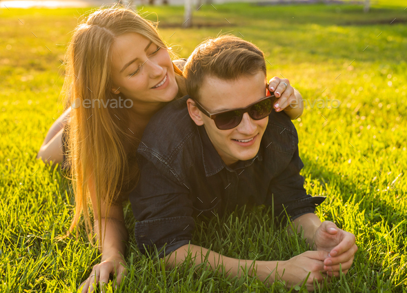 young couple having fun and playing in grass. woman lying over her lover, smiling - Stock Photo - Images